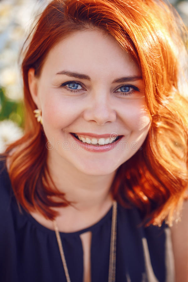 Closeup portrait of middle aged white caucasian woman with waved curly red hair in black dress looking in camera stock photography
