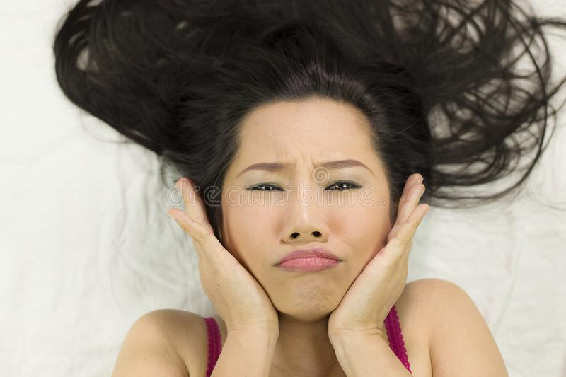Closeup portrait of moody asian women  lying on ground with black long hair. acting upset , unhappy stock images