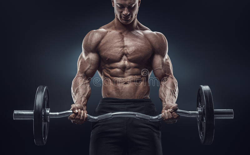 Closeup portrait of a muscular man workout with barbell at gym. Brutal bodybuilder athletic man with six pack, perfect abs, shoulders, biceps, triceps and stock photography