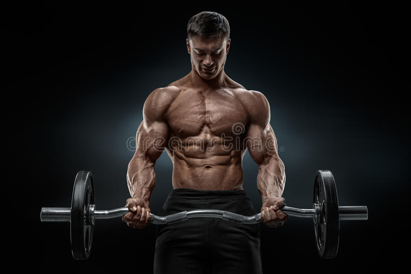 Closeup portrait of a muscular man workout with barbell at gym. Brutal bodybuilder athletic man with six pack, perfect abs, shoulders, biceps, triceps and stock image