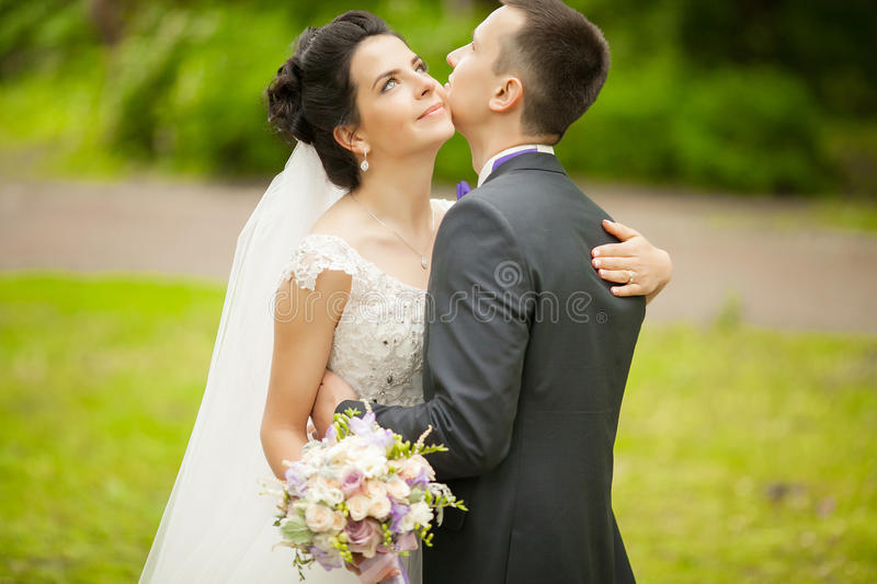 Closeup portrait of newly married couple hugging at park. stock image