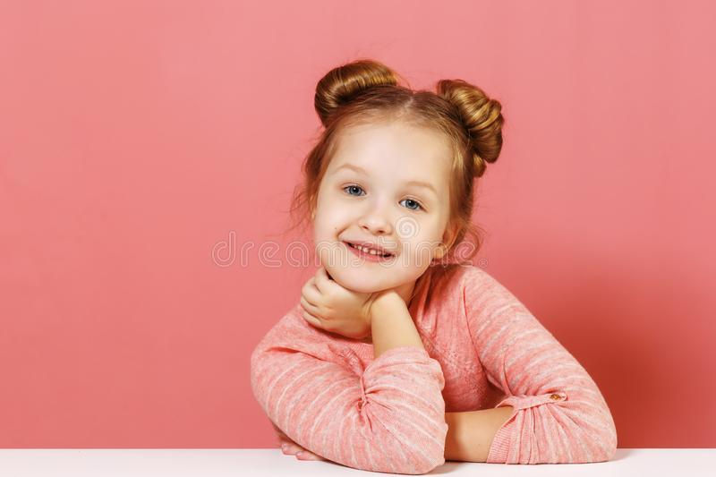 Closeup portrait of nice cute attractive charming cheerful little baby girl with buns in her hair over pink background. royalty free stock photo