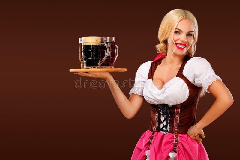 Closeup portrait of Oktoberfest girl - waitress, wearing a traditional Bavarian dress, serving big beer mugs on brown stock photo
