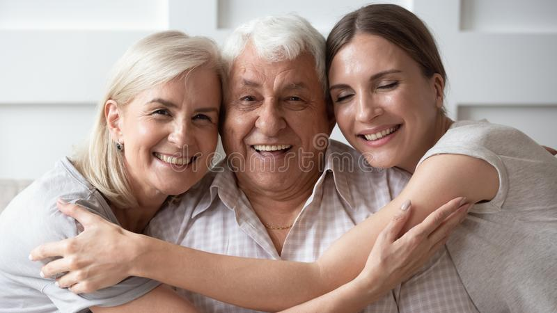 Closeup portrait old father middle-aged mother adult daughter. Horizontal banner close up image of three-generation family portrait happy beautiful faces, adult royalty free stock image