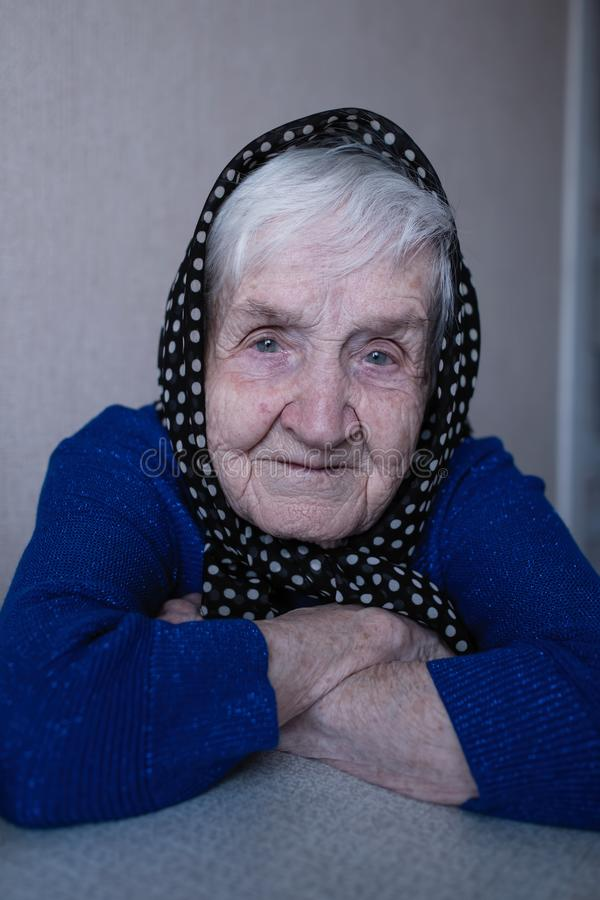 Closeup portrait of an pleasant old woman with a scarf on her head royalty free stock images