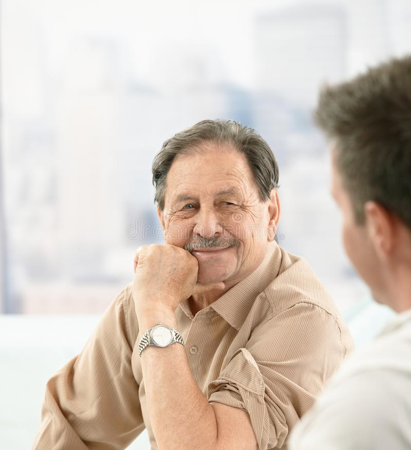 Closeup portrait of older patient at doctor. Closeup portrait of older patient smiling at doctor on consultation stock photos
