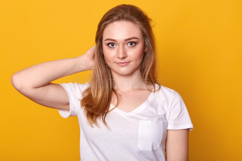 Closeup portrait of positive energetic young lady touching her hair with one hand, looking directly at camera, having pleasant royalty free stock photos