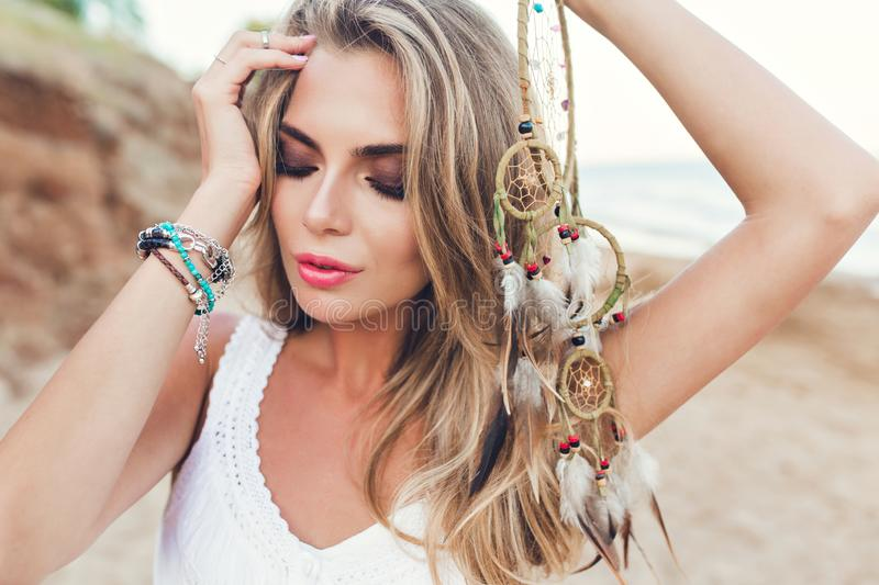 Closeup portrait of pretty blonde girl with long hair on beach. She wears white dress, holds ornamentation with feathers. Closeup portrait of pretty blonde girl royalty free stock images