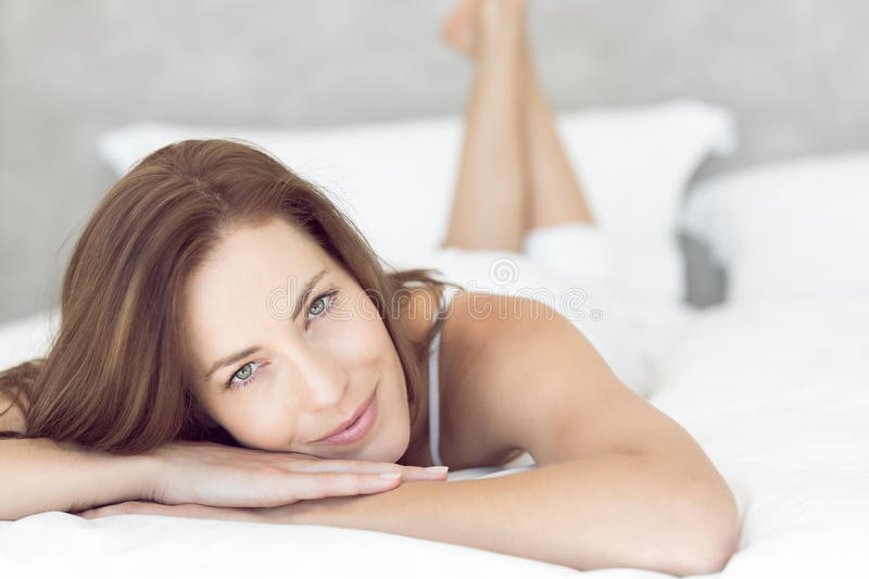 Closeup portrait of a pretty smiling woman lying in bed stock photos