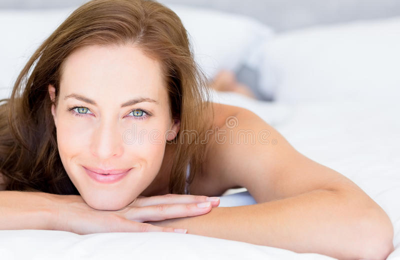 Closeup portrait of a pretty woman lying in bed royalty free stock photography