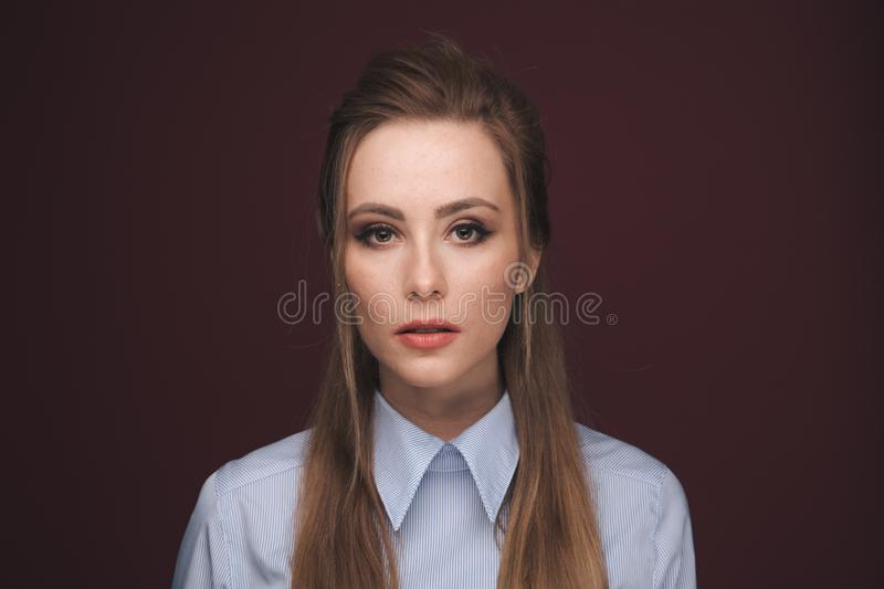 Closeup portrait of pretty yong woman with bright makeup in a studio isolated over dark pink background. stock photo