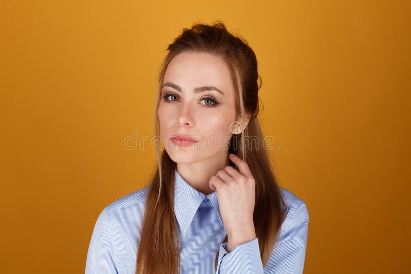 Closeup portrait of pretty yong woman with bright makeup in a studio  over the yellow background. royalty free stock images