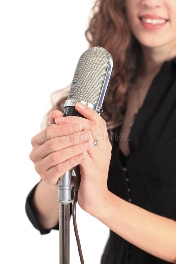 Closeup portrait of a pretty young female star performer holding old fashioned microphone royalty free stock photo
