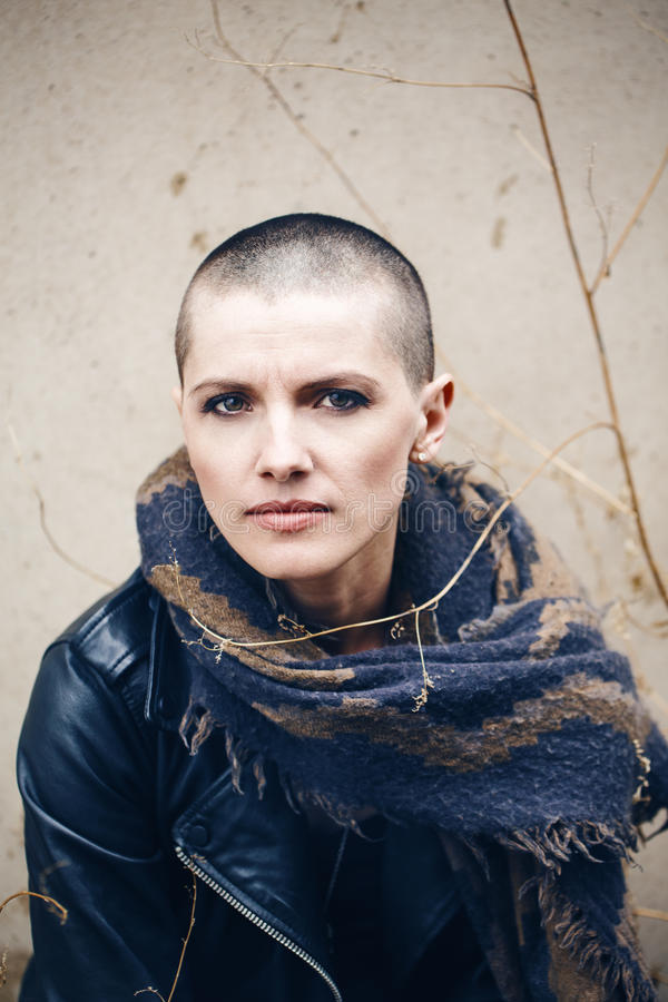 Closeup portrait of sad beautiful Caucasian white young bald girl woman with shaved hair head in leather jacket and scarf. Shawl, spiritual mood state of mind stock photography