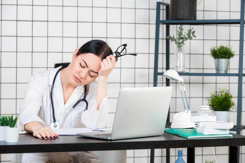 Closeup portrait sad unhappy health care professional with headache stressed sleepy holding cup of coffee. Nurse doctor stock image