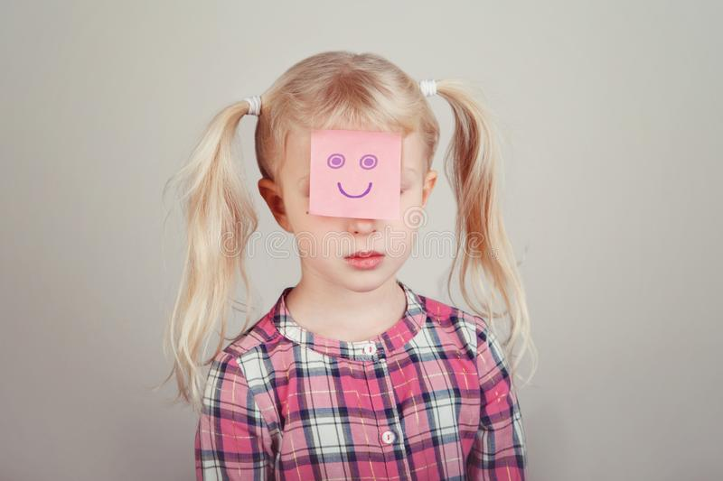 Sad unhappy white blonde Caucasian preschool girl with funny sticky note paper on her face. Closeup portrait of sad unhappy white blonde Caucasian preschool girl stock photography