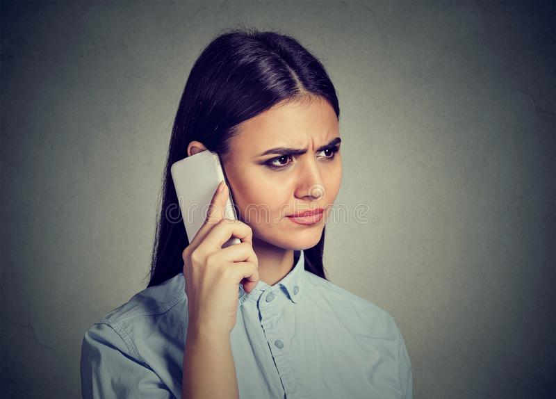 Closeup portrait, sad, unhappy woman talking on phone. Isolated on gray background. Negative human emotions, feelings royalty free stock images