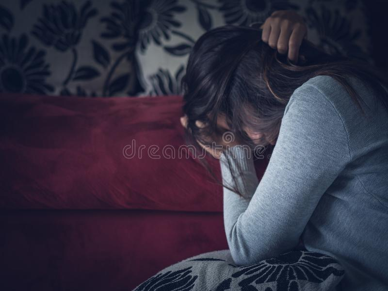 Closeup portrait of sad young woman sitting by sofa at home. royalty free stock images
