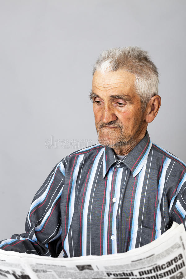 Closeup portrait of a senior man standing and reading a newspap royalty free stock photos
