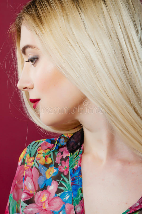 Closeup Portrait of Sensual Blonde with Professional Makeup and Colorful Shirt in Studio on Pink Background. royalty free stock images