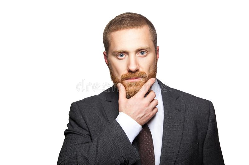 Closeup portrait of serious calm handsome businessman with facial beard in black suit standing, relaxed, touching his face and royalty free stock photos