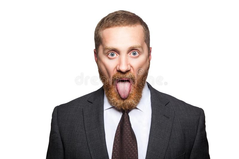 Closeup portrait of serious handsome businessman with facial beard in black suit and tie, standing and looking at camera with big. Eyes and tongue out. indoor stock photos