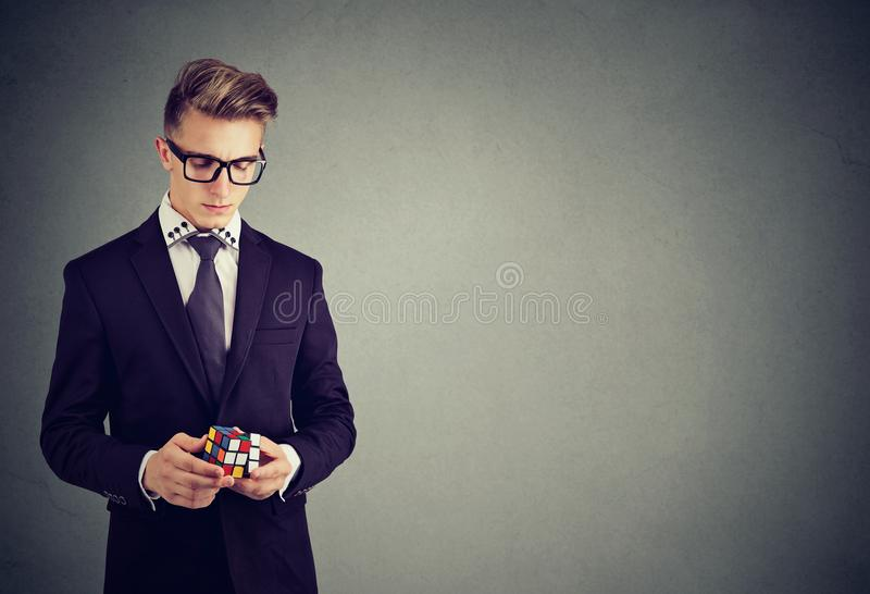 Closeup portrait of serious man in eyeglasses holding rubik cube. Closeup portrait of serious young man in eyeglasses holding rubik cube royalty free stock photography