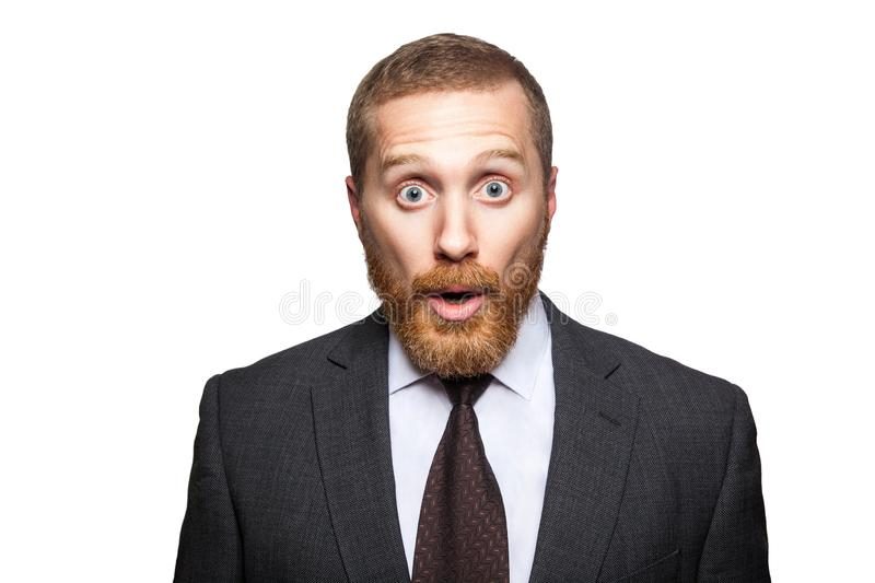 Closeup portrait of shocked handsome businessman with facial beard in black suit standing and looking at camera with big eyes and. Open mouth. indoor studio stock photography