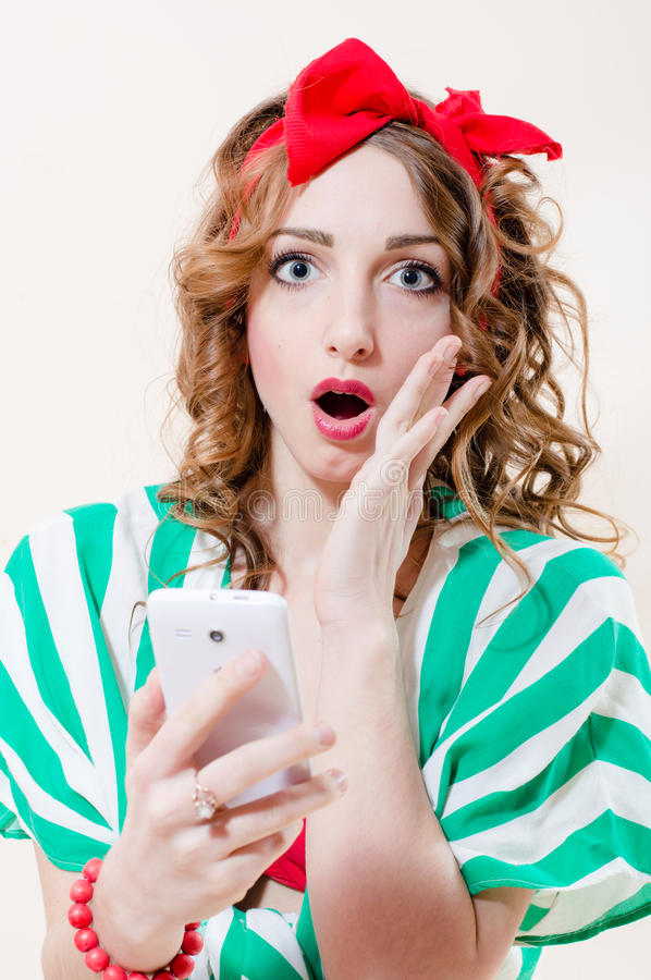 Closeup portrait of shocked holding mobile cell phone pinup girl beautiful blond with blue eyes young lady with red ribbon royalty free stock photo