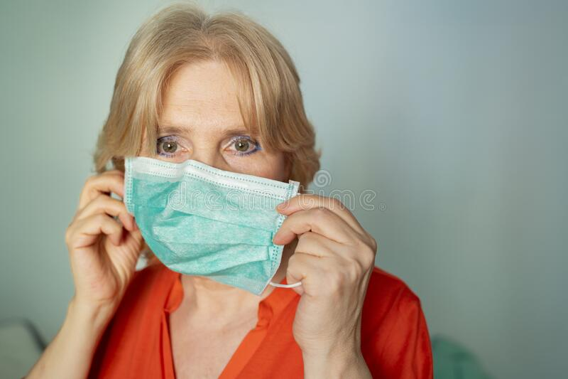 Older woman taking off surgical mask mask stock photography