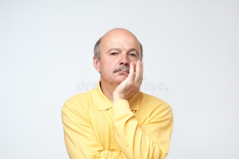 Closeup portrait of sleepy mature man in yellow t-shirt, funny guy placing head on hand, unhappy looking at camera. royalty free stock photo