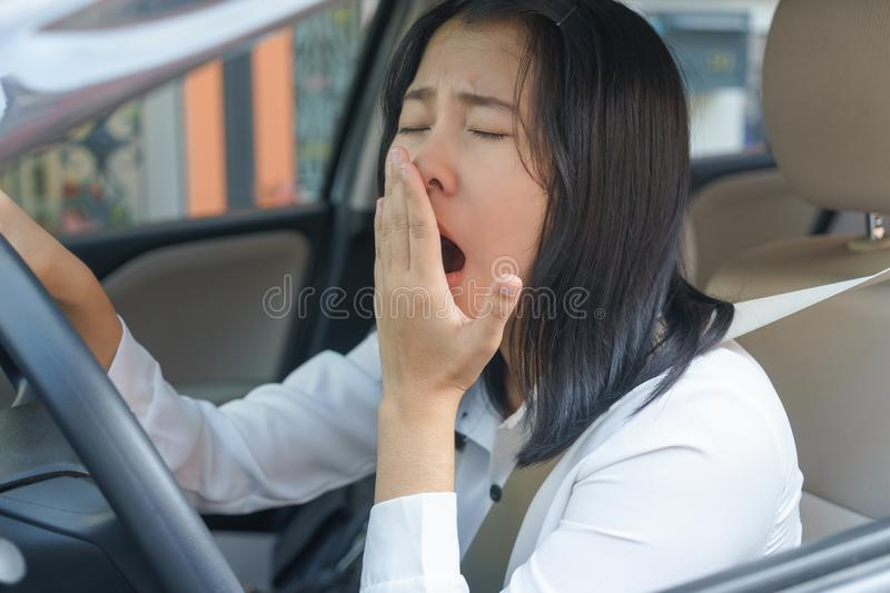 Closeup portrait sleepy, yawn, close eyes young woman driving he. R car after long hour trip, Sleep deprivation, accident concept royalty free stock photography