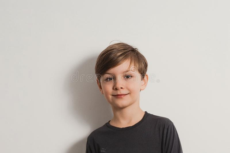 A closeup portrait of a smiling cute boy in a grey shirt royalty free stock image
