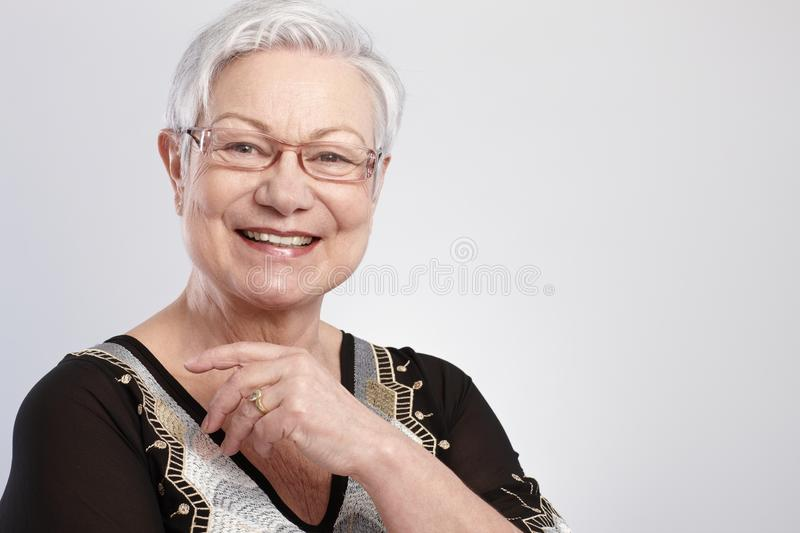Closeup portrait of smiling elderly lady. In glasses stock photos