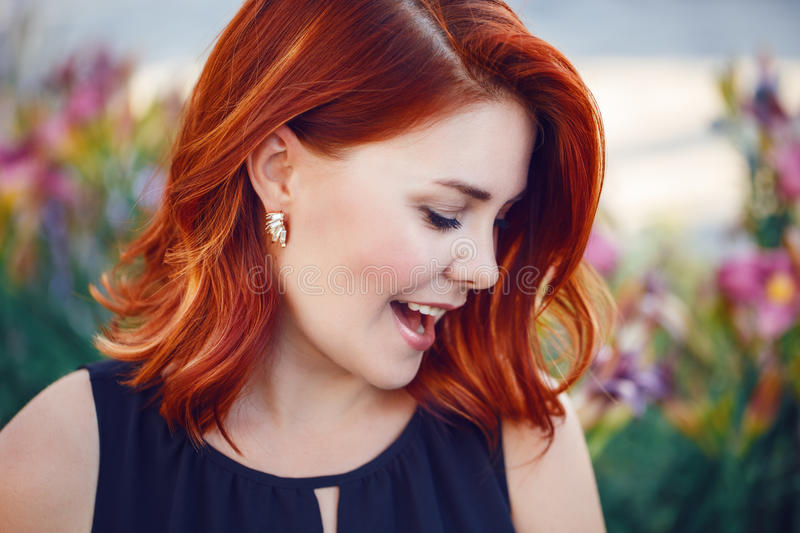 Closeup portrait of smiling laughing flirty middle aged white caucasian woman with waved curly red hair in black dress royalty free stock photos