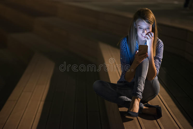 Closeup portrait smiling or laughing young freelancer woman looking at phone seeing good news or photos with nice emotion stock photography