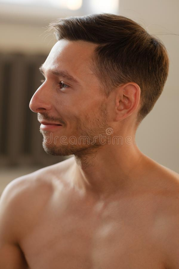Closeup portrait of a smiling yoga trainer and stubble on his face. Closeup portrait of a smiling yoga trainer with naked torso and stubble on his face stock image