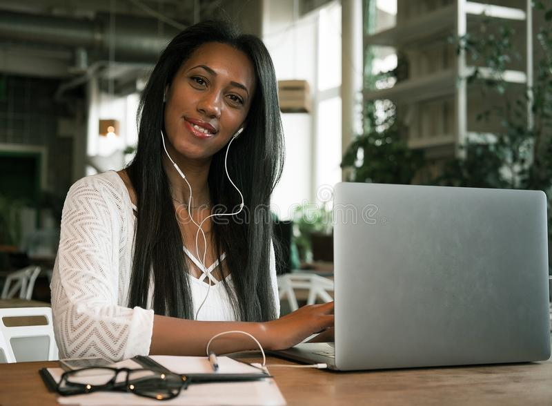 Closeup portrait of smiling young african woman sitting in a cafe with laptop stock photo