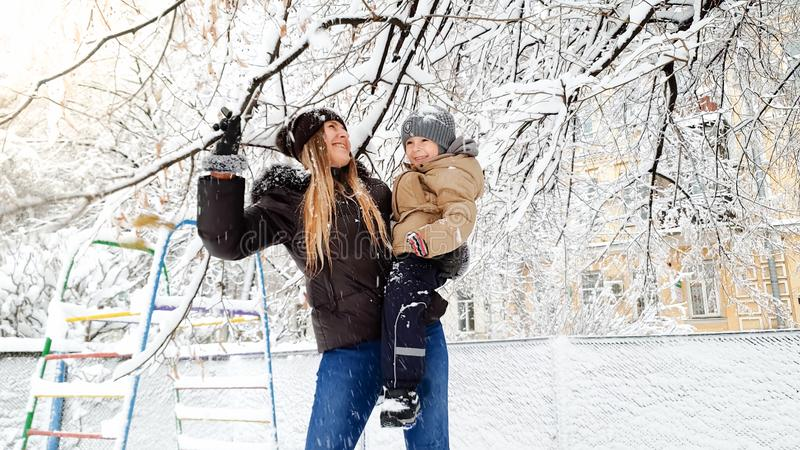 Closeup portrait of smiling young mother with her pretty son in jacket and hat playing with snow covered tree on the royalty free stock image