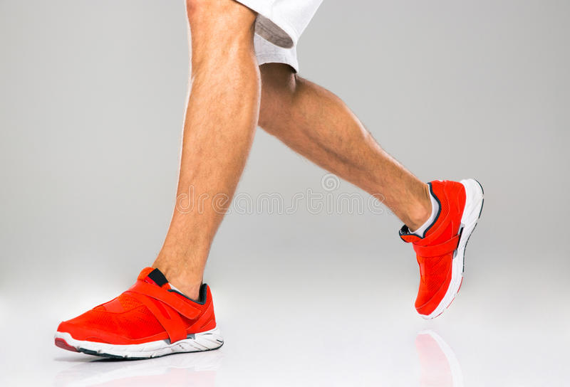 Closeup portrait of a sports male legs. Over gray background stock images