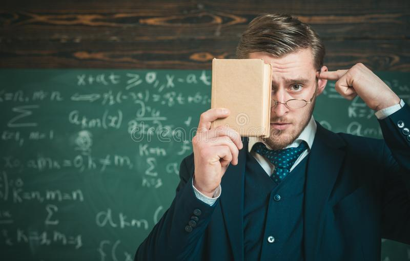 Closeup portrait of student holding book in front of his face and pointing at his head with other hand. Thoughtful stock image