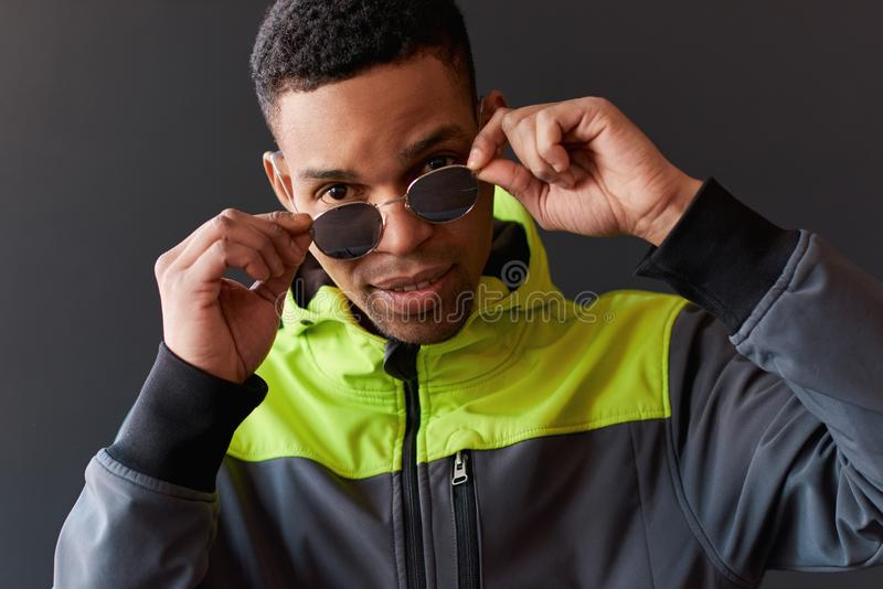 Closeup portrait of stylish African American man looking through posing for mirror sunglasses, posing on black studio wall. royalty free stock photo