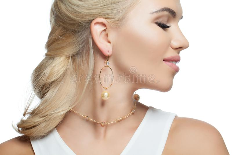 Closeup portrait of stylish woman isolated on white background. Beautiful girl with gold jewelry royalty free stock image
