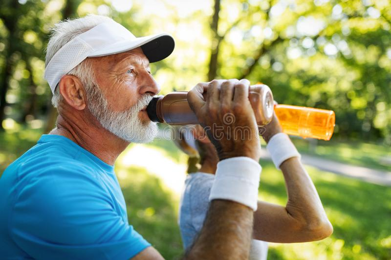 Closeup portrait, thirsty senior man drinking water outside stock photos
