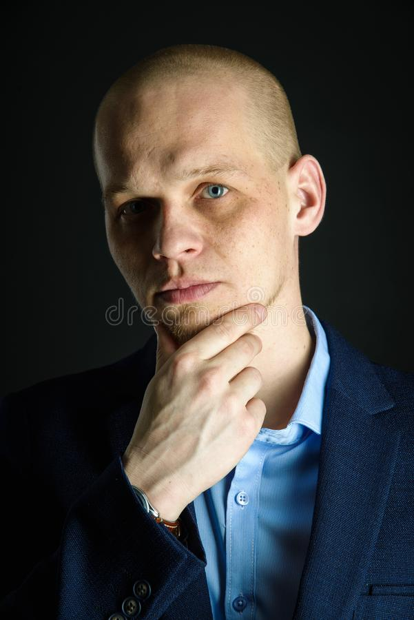 Closeup portrait of thoughtful man in suit being worried about something on black background stock photo