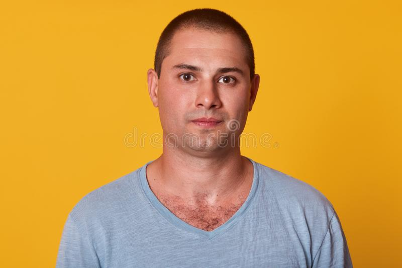 Closeup portrait of thoughtful serious handsome man standing isolated over yellow background in studio, looking directly at camera stock photography