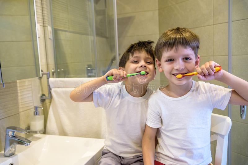 Closeup portrait of twins kids toddler boy brother in bathroom toilet washing face hands brushing teeth with toothbrush playing. With water, lifestyle home royalty free stock photography