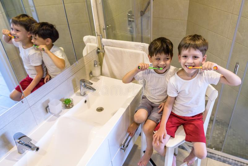 Closeup portrait of twins kids toddler boy brother in bathroom toilet washing face hands brushing teeth with toothbrush playing. With water, lifestyle home royalty free stock photos