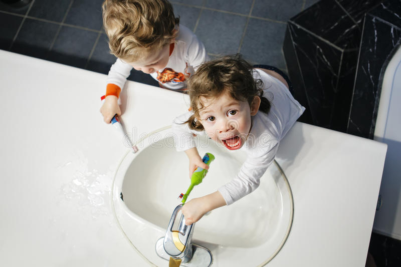 Closeup portrait of twins kids toddler boy girl in bathroom toilet washing face hands brushing teeth with toothbrash royalty free stock photography
