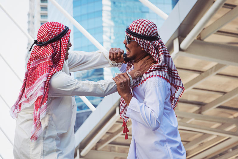 Closeup portrait of two Arab guys fighting, Aggressive behavior, on city background.  royalty free stock photos